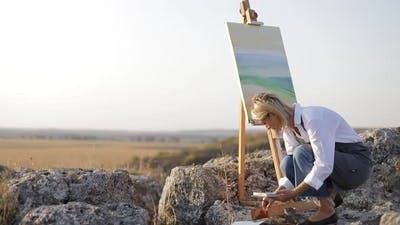 A professional artist paints a picture with oil paints