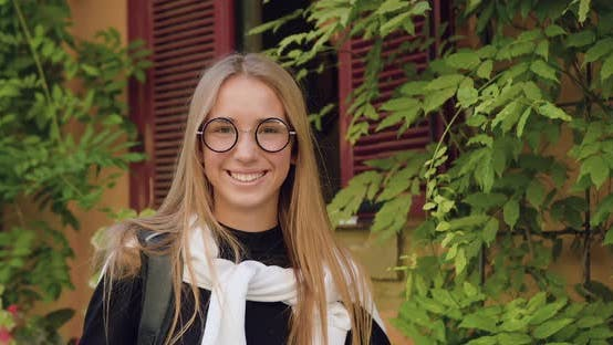 Thumbnail for Girl in Stylish Glasses Standing in front of Camera Near Ancient City Building