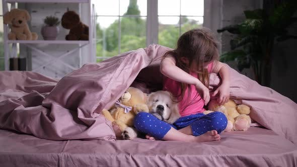 Thumbnail for Joyful Child Hiding Under Blanket with Puppy Pet