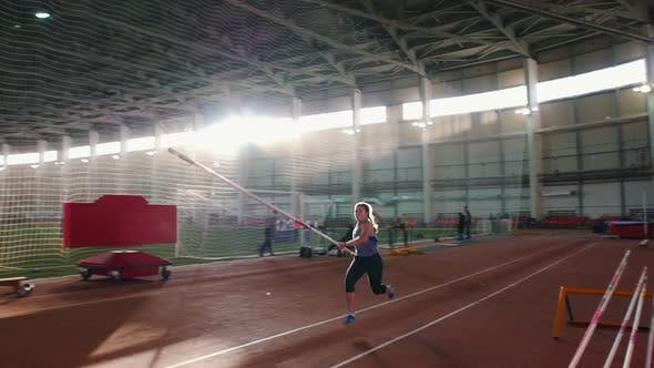 Thumbnail for Pole Vaulting Indoors - Young Woman with Pigtails Jumping Over the Bar and Touches the Bar