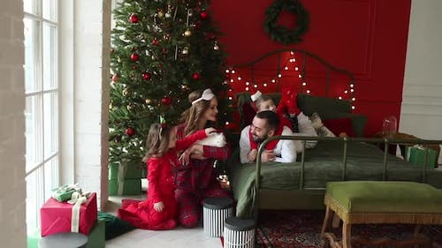 Happy Young Family with Kids Wearing Pyjamas Petting a Pet Rabbit Near Christmas Tree in Cozy