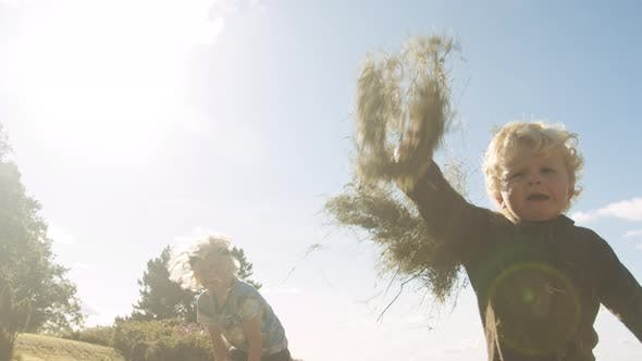 Thumbnail for Toddler Throwing Meadow Grass To Camera