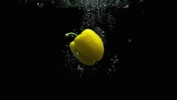 Thumbnail for Yellow Bell Pepper Falling Into Water With Lot Of Air Bubbles Black Background