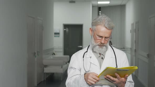 Thumbnail for Friendly Senior Doctor Smiling To the Camera Standing at Hospital Hallway