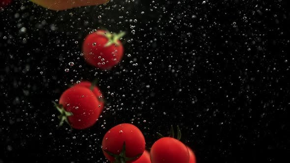 Cover Image for Cherry Tomatoes and Red Yellow Paprika Bell Peppers Falling Into Water with Air Bubbles