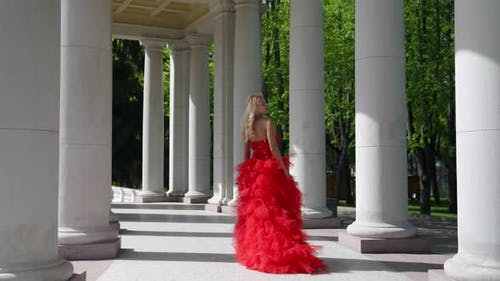 a Blonde with Big Breasts in a Red Fluffy Dress and with a Rose Poses Among the Columns
