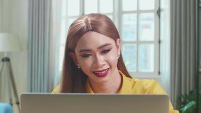 Asian Young Transgender Woman Working With Laptop Computer In Living Room
