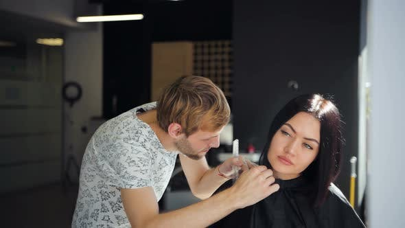 The Hairdresser Does a Haircut with Scissors of Hair To a Young Girl in a Beauty Salon