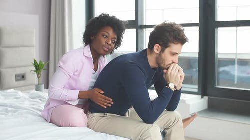 Relationship Problems. Frustrated Young Mixed Raced Couple Sitting in Bed