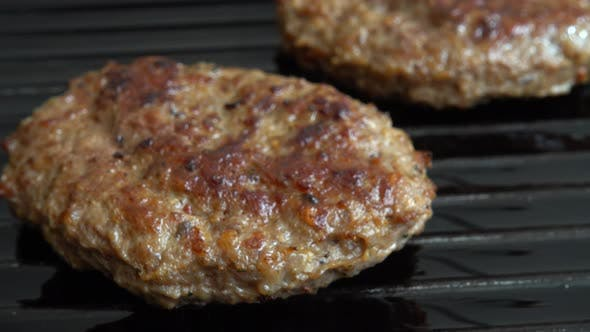 The fried cutlet for hamburger rotates on the grill pan.