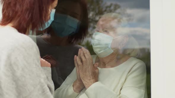 Young Woman In Medical Mask Talks Through The Window With An Elderly Woman In Medical Mask