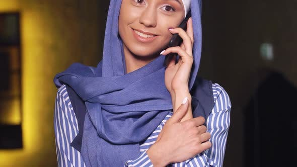 Thumbnail for Attractive Muslim Woman in Hijab Talking at Mobile Phone