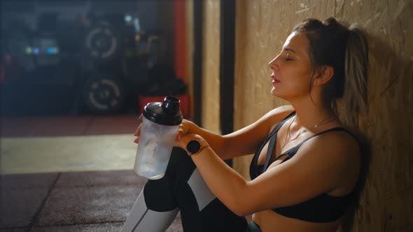 Cover Image for Fitness Woman Drinking Water From Bottle. Muscular Young Female at Gym Taking a Break From Workout.