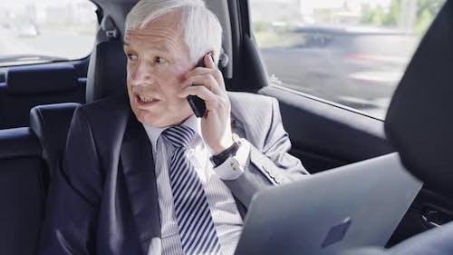 Senior Businessman Working in Car