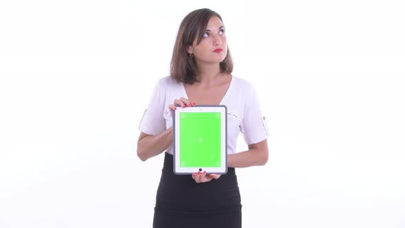 Thumbnail for Happy Beautiful Businesswoman Thinking While Showing Digital Tablet