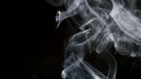 Thumbnail for Cigarette Smoke Lifts Up On A Dark Background