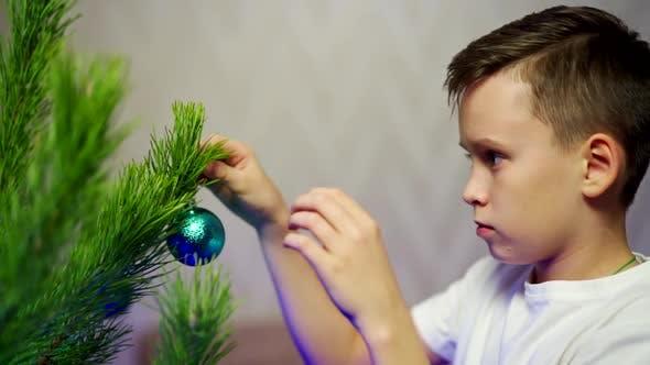 Kid schmücken Weihnachtsbaum. Porträt eines Jungen, der den Weihnachtsbaum schmückt
