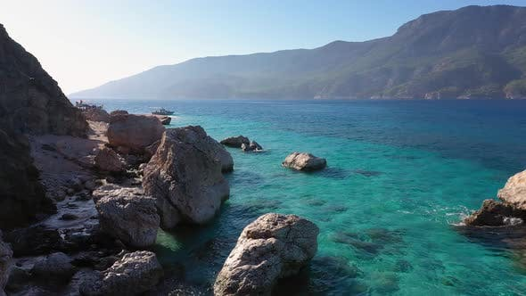 Panoramic Landscape of Rocky Seashore and Clear Sea Water with View of Mountains
