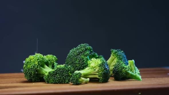 Fresh Green Broccoli Sprinkled with Salt Lying on Board