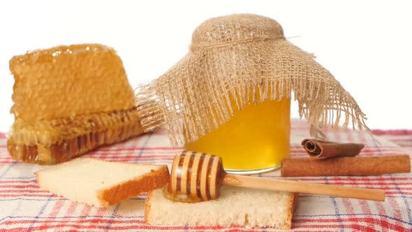 Thumbnail for Honey Spoon Dripper and Jar with Stick Pouring Over Toast Bread, Honeycomb on White