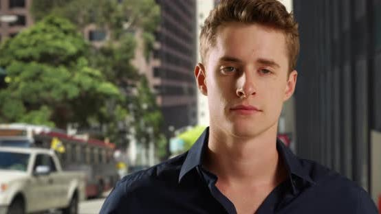 Thumbnail for Portrait of handsome white male standing on city sidewalk looking at traffic.  Young Caucasian man w