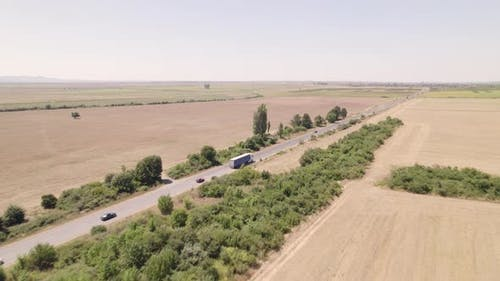 Highway with Transporting Truck with Wheat Field in the Background