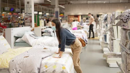 Young Woman in Face Mask Examining Orthopedic Mattress Before in Modern Furnishing Store