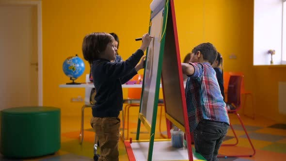 Creative Multicultural Boys Drawing on Easel Board