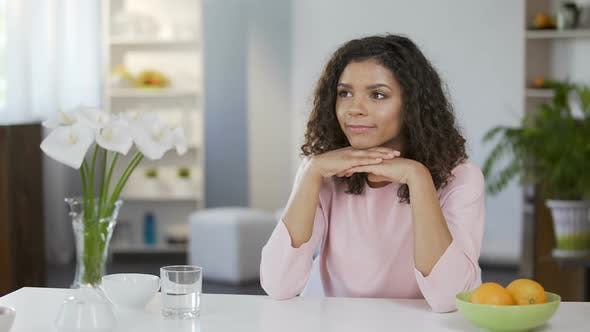 Thumbnail for Beautiful mixed race woman sitting at table and daydreaming, future plans