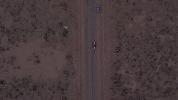Cover Image for AERIAL: Birds View Flight Over Lonely Abandoned Desert Road with Red Car Driving in the Distance