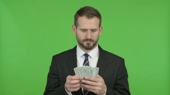 Thumbnail for Young Businessman Counting and Offering Money Against Chroma Key