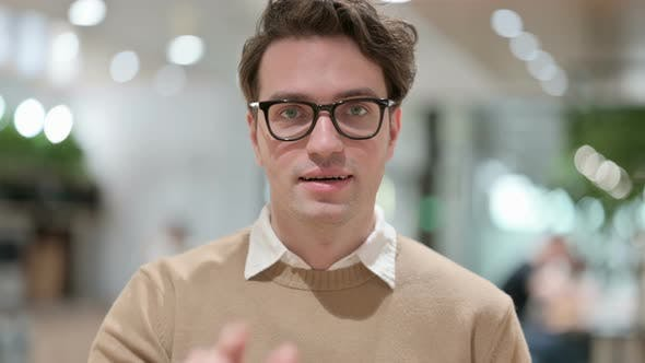 Young Male Designer Pointing at the Camera and Inviting