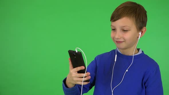 Thumbnail for A Young Cute Boy Listens To Music on a Smartphone with a Smile - Green Screen Studio