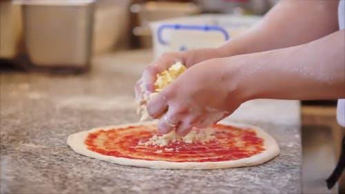 Eine echte Peperoni-Pizza, eine Methode ihrer Zubereitung, kocht der italienische Koch mit seinen Finger ein Real
