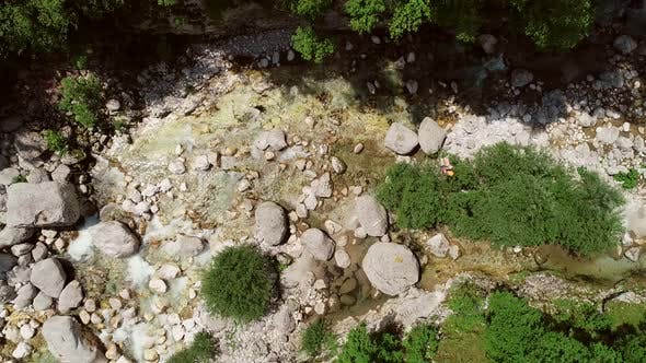 Thumbnail for Aerial view of a person passing through the Soca River on a zip line in Slovenia