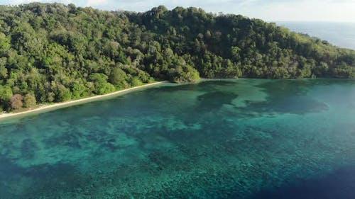 Aerial: flying over tropical Hatta island white sand beach Banda Islands Maluku