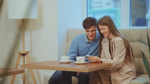 Loving Couple Looking at Smartphone in Cafe