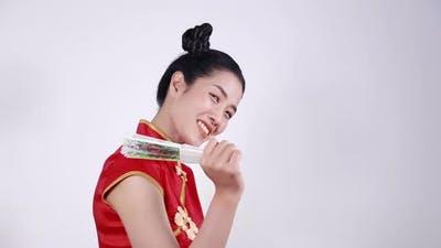 woman wearing chinese cheongsam dress and holding a chinese fan