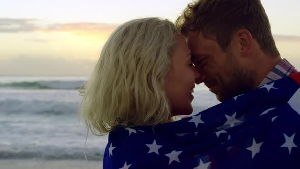 Thumbnail for Couple wrapped in american flag at beach during sunset 4k