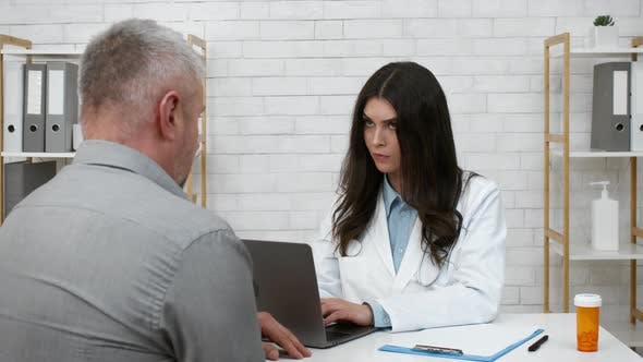 Senior Male Patient Complaining To Doctor About Symptoms In Clinic