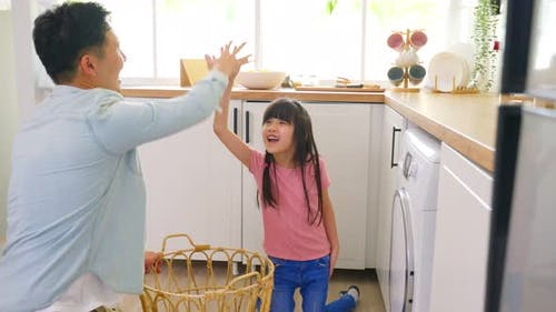 Asian young little cute girl child help and learn from parent dad to put laundry in washer appliance