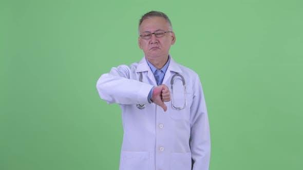 Sad Mature Japanese Man Doctor Giving Thumbs Down