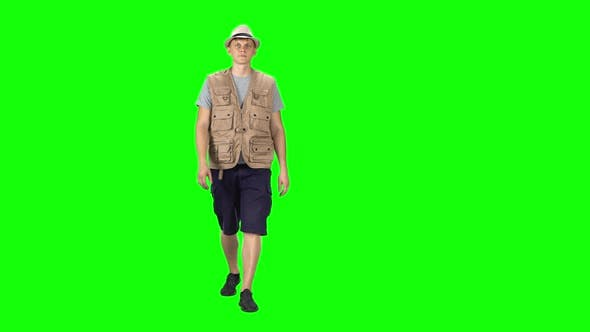Thumbnail for Young Man in a Grey T-shirt, Sleeveless Shirt, Shorts, Sneakers and Hat Going Against a Green