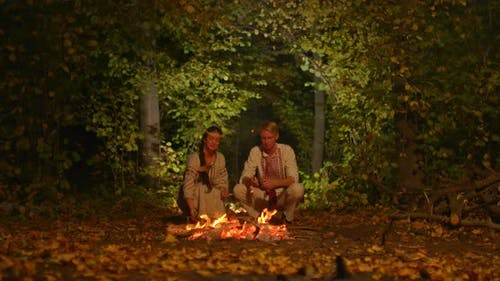 Handsome Man Woman Slavic Costumes Sit By Fire Throw Leaves Into Fire
