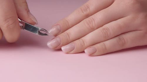 Closeup Woman Hand on Pink Makes Manicure for Herself