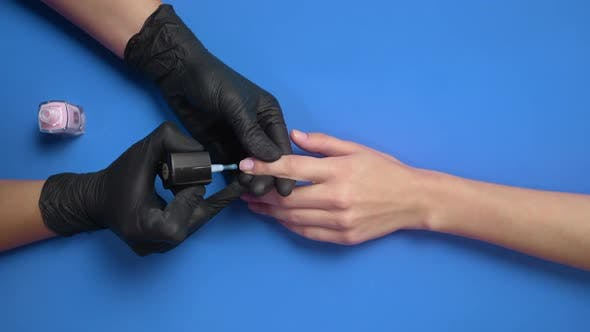 Thumbnail for Manicurist in Black Rubber Gloves Paints Client's Nails with Transparent Protective Nail Polish