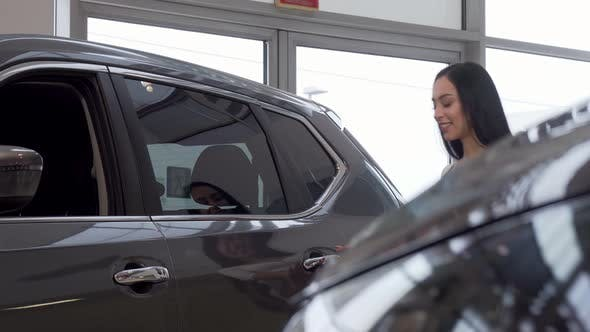 Thumbnail for Woman Smiling To the Camera, While Examining Cars on Sale at the Dealership