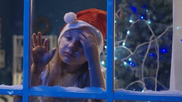 Thumbnail for Charming Girl Through Window in Santa Hat
