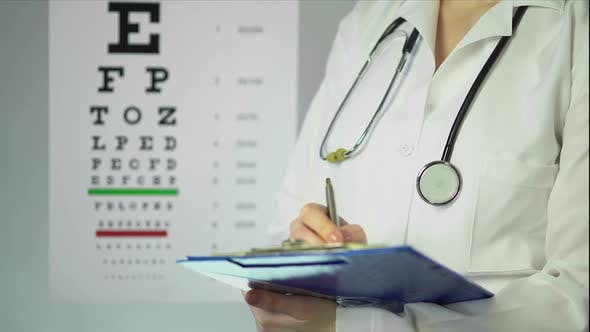 Hard-Working Optician Prescribing Medication to Patient at Clinic, Healthcare