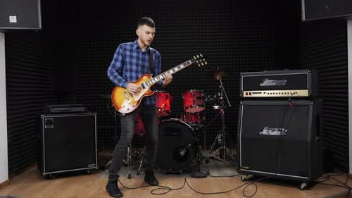 Guitarist is playing solo on electric guitar on stage in recording vocal studio